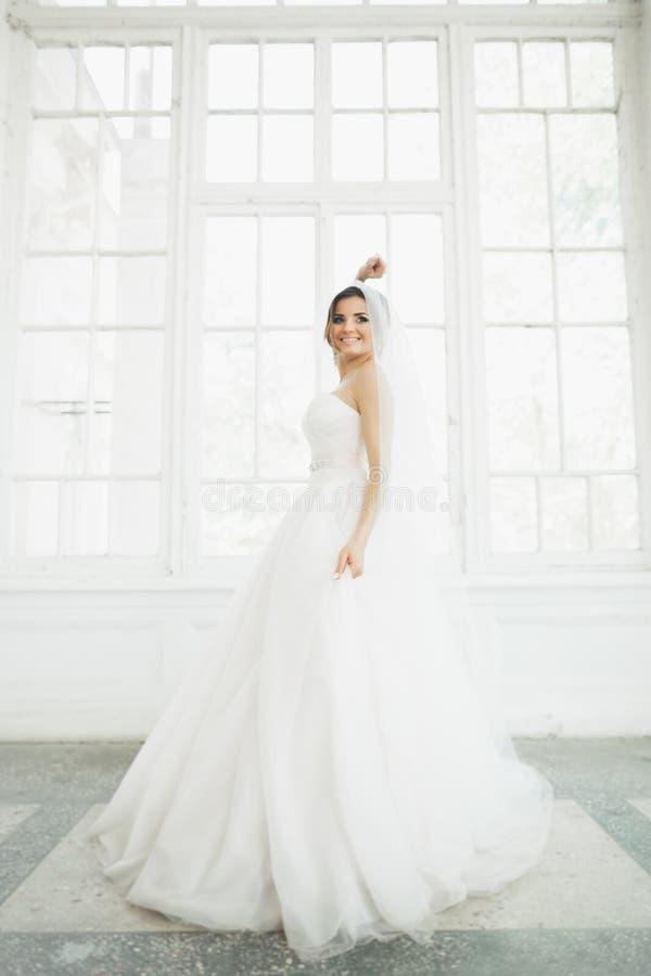 Belle jeune mariée dans la robe de mariage avec la longue pleine jupe, le fond blanc, la danse et le sourire photo libre de droits