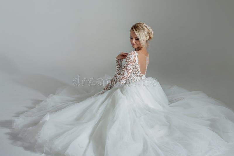 Belle jeune mariée dans la robe de mariage luxueuse, séance dans de cercle des jupes longtemps Fond blanc, vue supérieure image stock