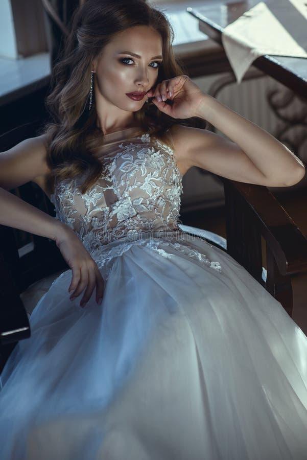 Belle jeune mariée dans la robe l'épousant ligne un luxueuse se reposant dans la chaise de bras de cru dans la pose décontractée photographie stock