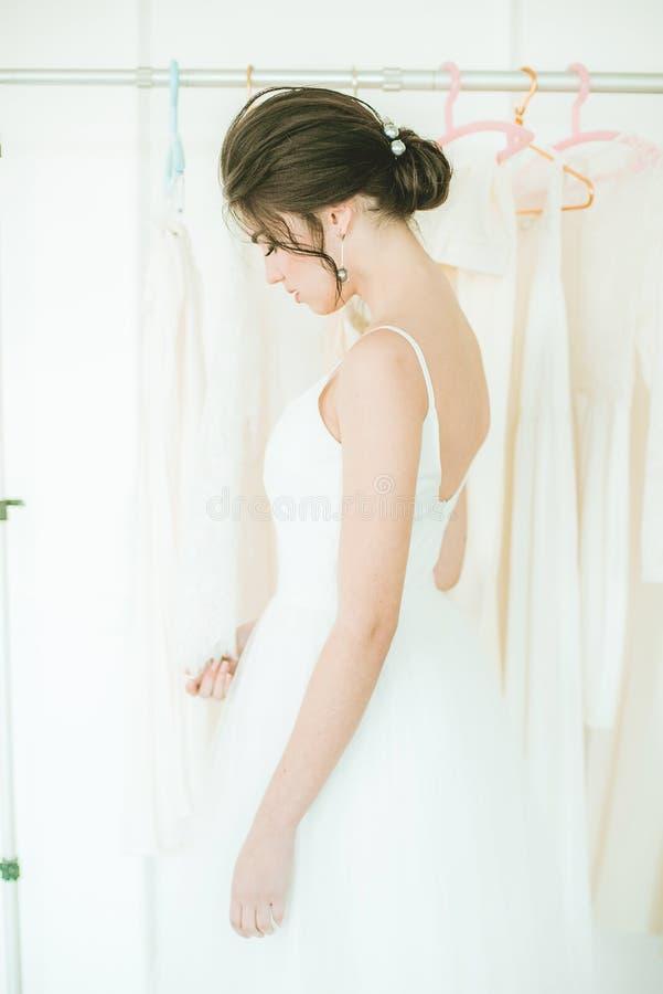 Belle jeune jeune mariée dans une robe blanche dans le salon sur le fond d'autres robes photographie stock