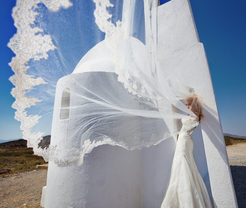 Belle jeune mariée dans une robe de mariage en Grèce avec un long voile photos stock