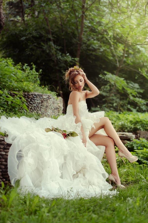 Belle jeune mariée de femme avec de longues jambes appréciant en nature images libres de droits