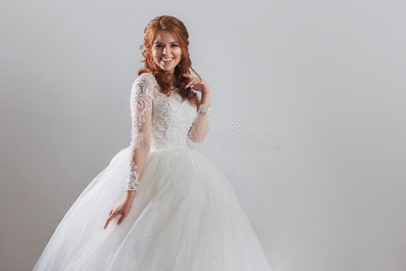 Belle jeune mariée de jeune femme dans la robe de mariage somptueuse Fond clair photo stock