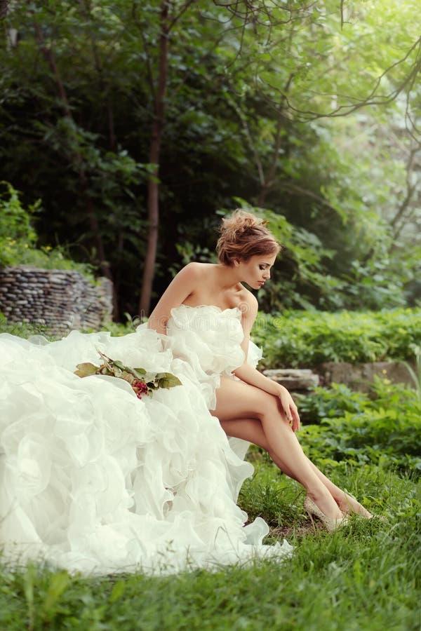 Belle jeune mariée de femme regardant ses longues jambes en nature dans la forêt photographie stock