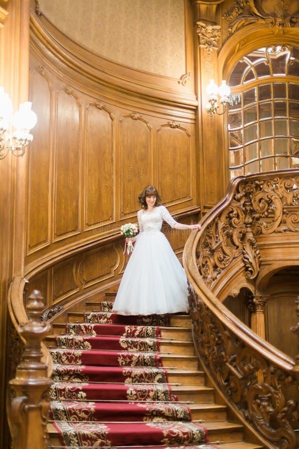 Belle jeune mariée descendant les escaliers avec un bouquet dans des mains à l'intérieur en bois riche photo stock