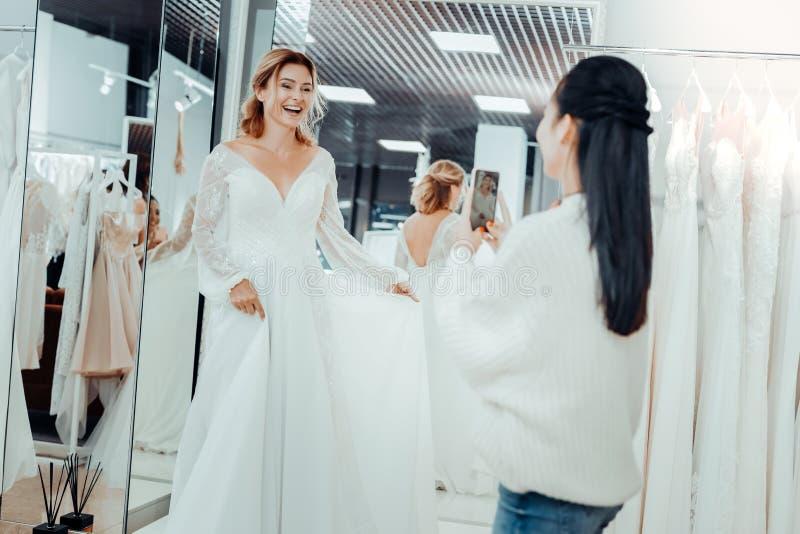 Belle jeune mariée et sa demoiselle d'honneur prenant des photos d'une robe photos stock