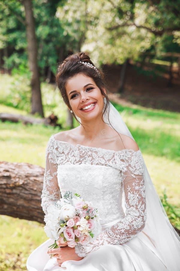 Belle jeune mariée heureuse avec le bouquet des fleurs en parc photo stock