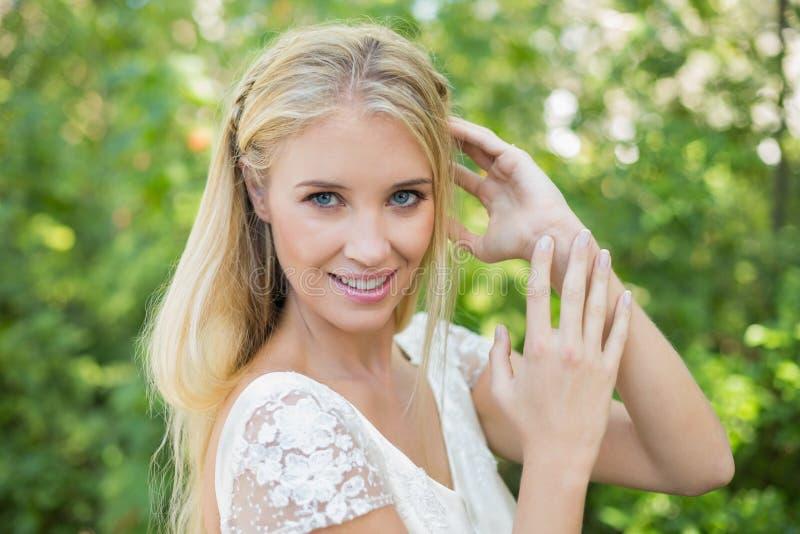Belle jeune mariée heureuse touchant ses cheveux regardant l'appareil-photo photographie stock libre de droits