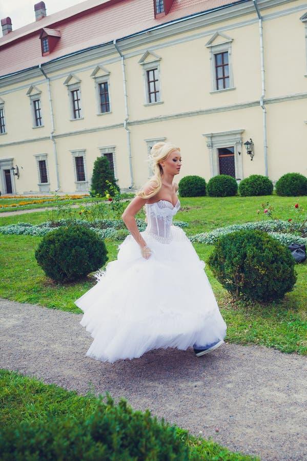 Belle jeune mariée marchant en parc près du château photos stock