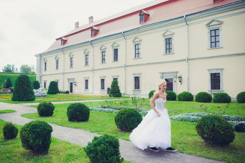 Belle jeune mariée marchant en parc près du château photo libre de droits