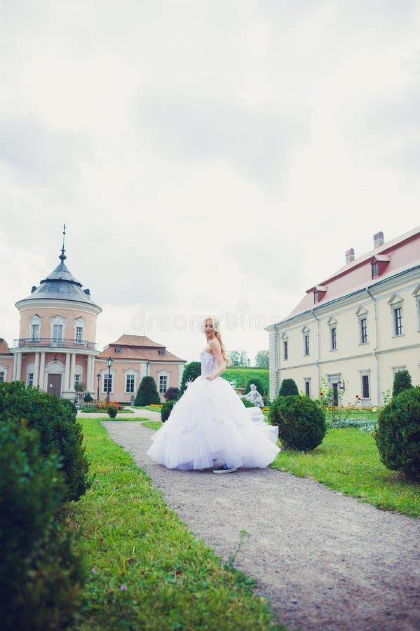 Belle jeune mariée marchant en parc près du château images stock