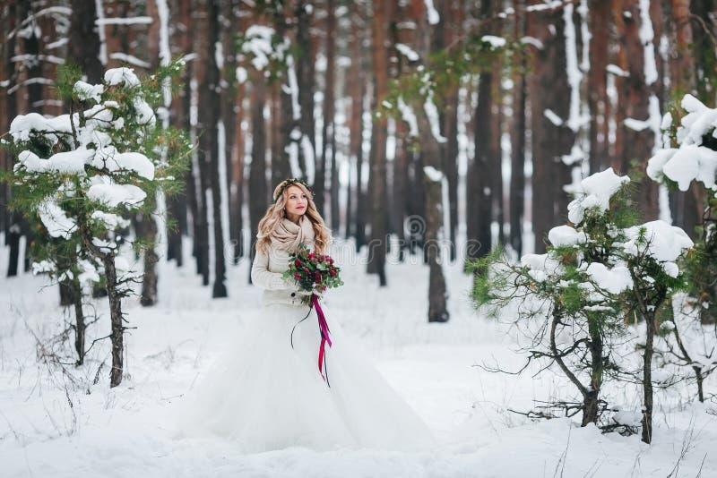 Belle jeune mariée posant avec le bouquet dans le mariage neigeux d'hiver de forêt dessin-modèle photo libre de droits