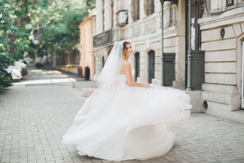 Belle jeune mariée posant dans la robe de mariage dehors photographie stock libre de droits