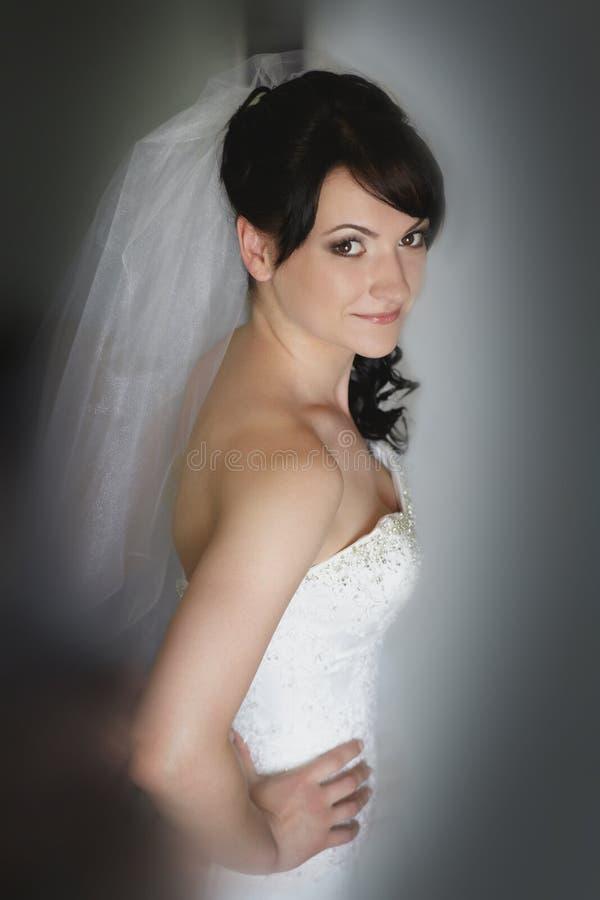 Belle jeune mariée posant pour l'appareil-photo dans le studio photo stock