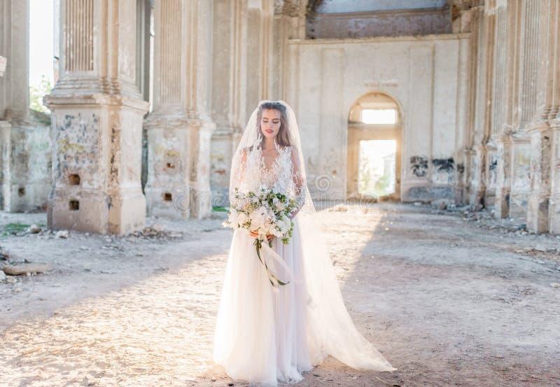 Belle jeune mariée romantique dans la pose de luxe de robe de la belle architecture photos libres de droits