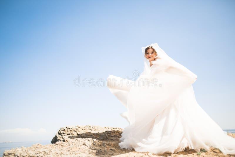 Belle jeune mariée romantique dans la robe blanche posant sur la mer de fond images libres de droits