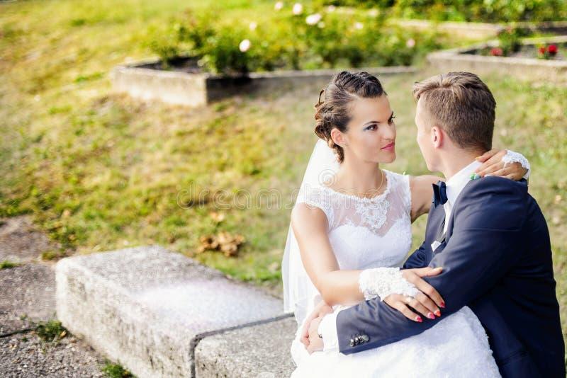 Belle jeune mariée s'asseyant sur des jambes de mariés photos stock