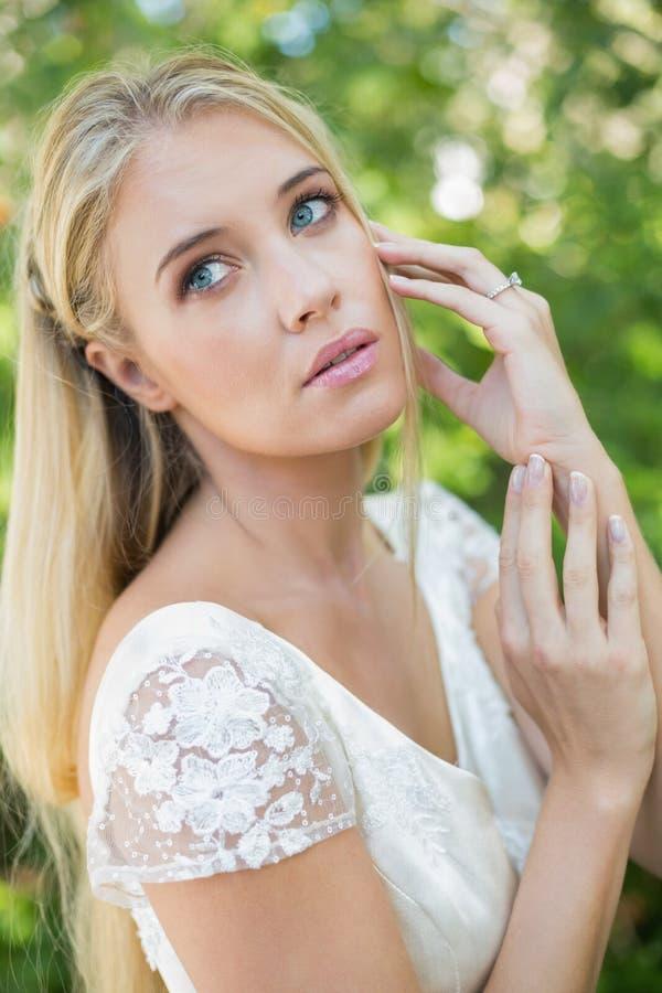 Belle jeune mariée satisfaite touchant ses cheveux regardant loin images libres de droits