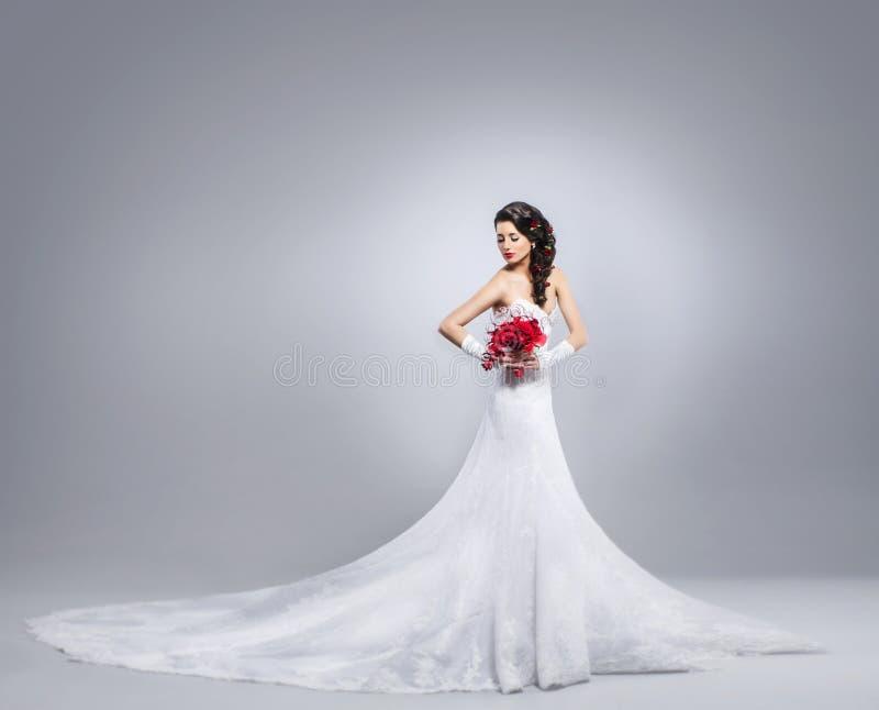 Belle jeune mariée se tenant avec un bouquet de fleur image libre de droits