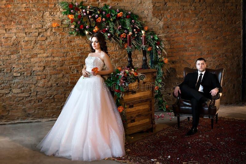 Belle jeune mariée se tenant dans une robe blanche intéressante photos stock