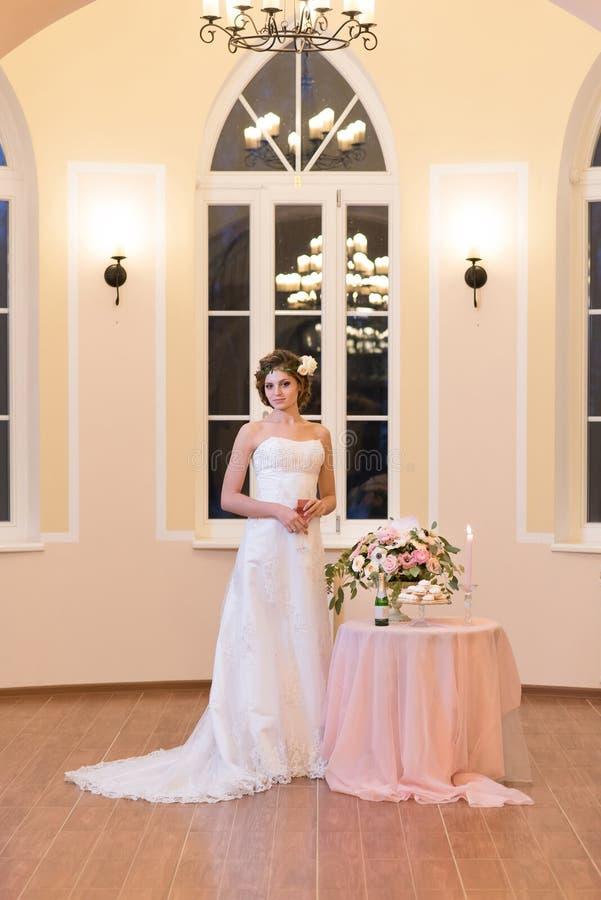 Belle jeune mariée se tenant dans une salle légère photo stock