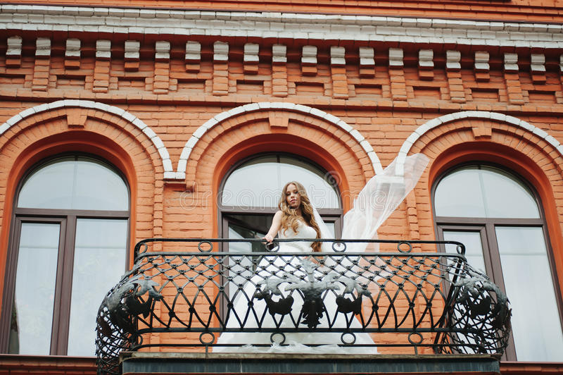 Belle jeune mariée se tenant sur le balcon en pierre images stock