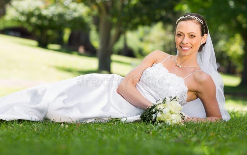 Belle jeune mariée se trouvant sur l'herbe en parc images stock