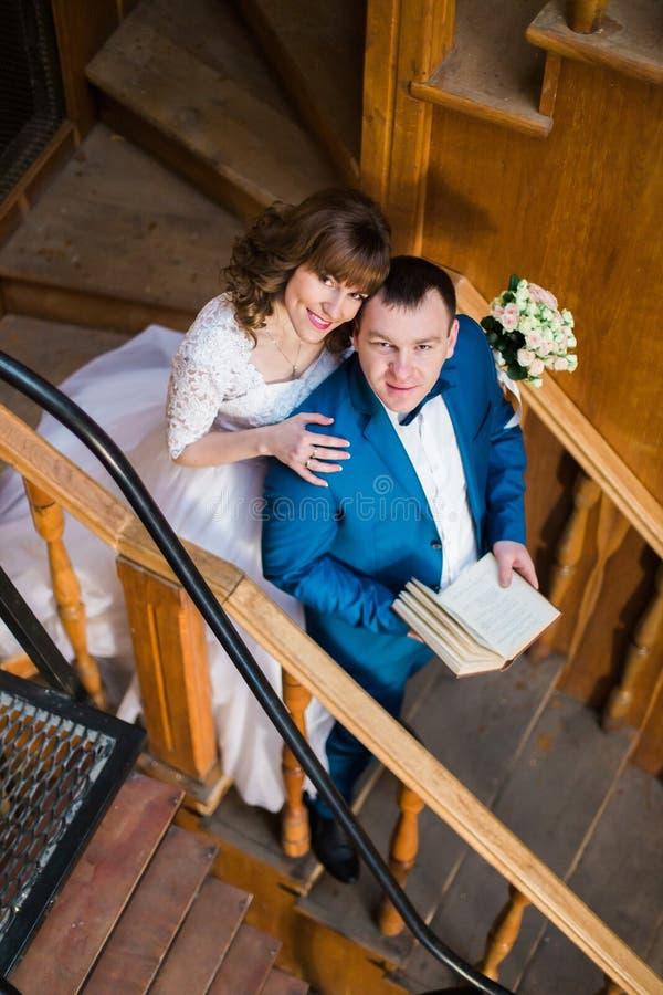 Belle jeune mariée sensuelle étreignant par derrière son marié beau tenant le livre aux escaliers en bois de la vieille bibliothè images stock