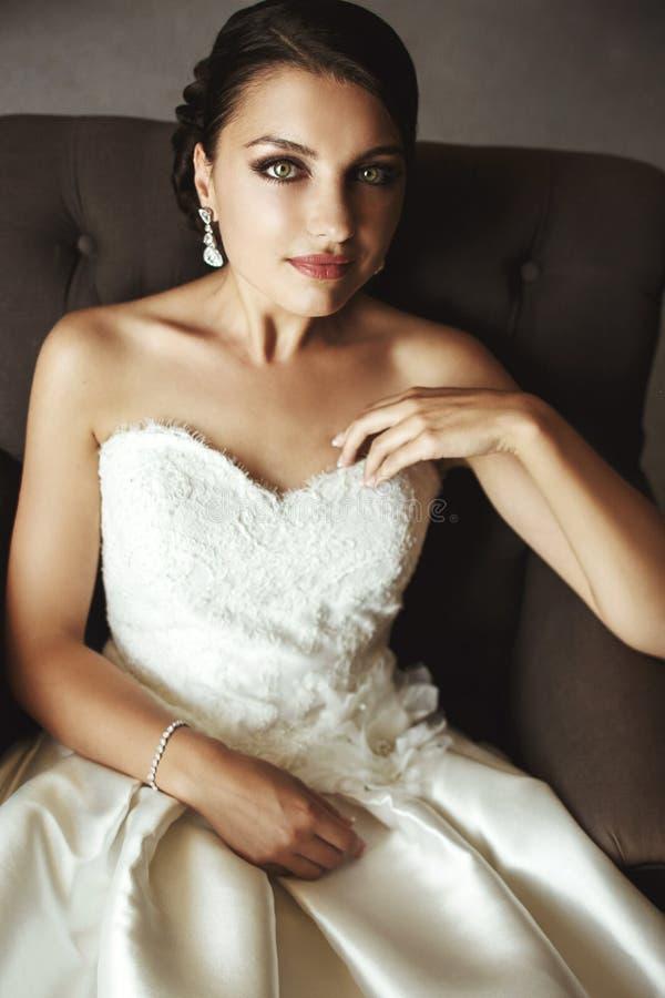 Belle jeune mariée sensuelle de brune dans la robe blanche se reposant sur le leath photo stock