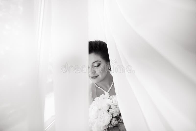 Belle jeune mariée sexy dans la robe blanche posant sous le rideau images stock