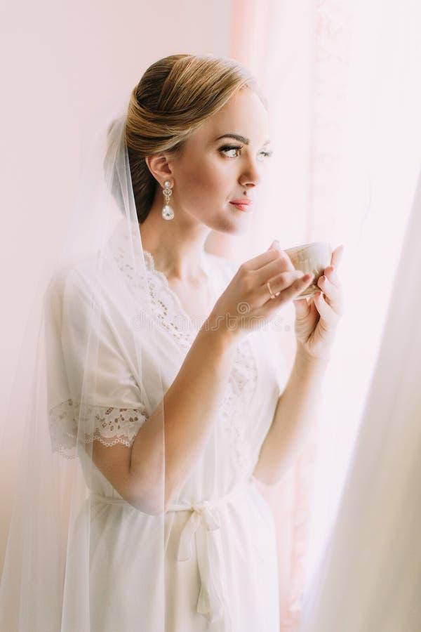 Belle jeune mariée tenant la tasse de thé tout en regardant par la fenêtre images libres de droits