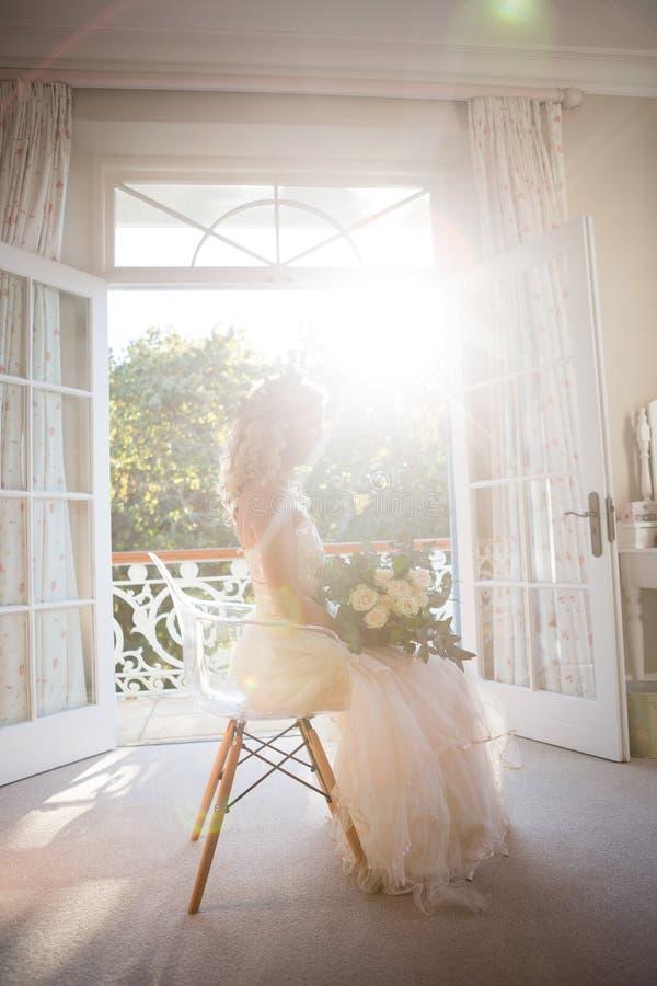 Belle jeune mariée tenant le bouquet tout en se reposant sur la chaise à la maison photos stock