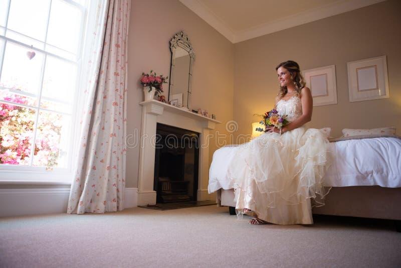 Belle jeune mariée tenant le bouquet tout en se reposant sur le lit à la maison photo libre de droits
