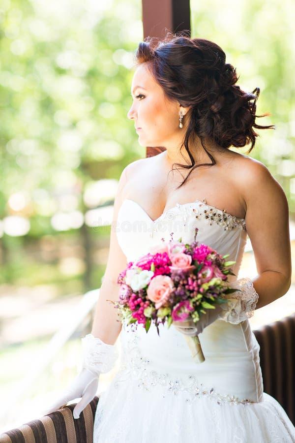 Belle jeune mariée tenant le grand bouquet de mariage photos libres de droits