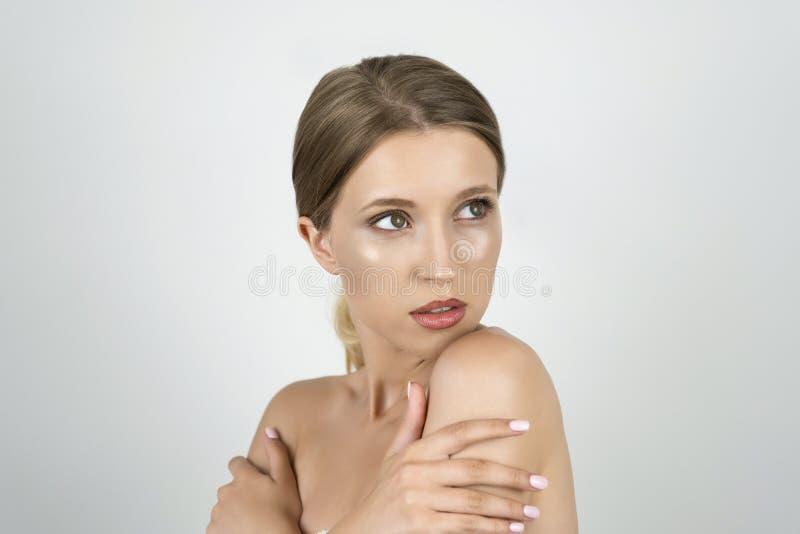 Belle jeune moitié blonde d'un tour de femme tenant des mains près des épaules étroites vers le haut du fond blanc d'isolement photographie stock libre de droits