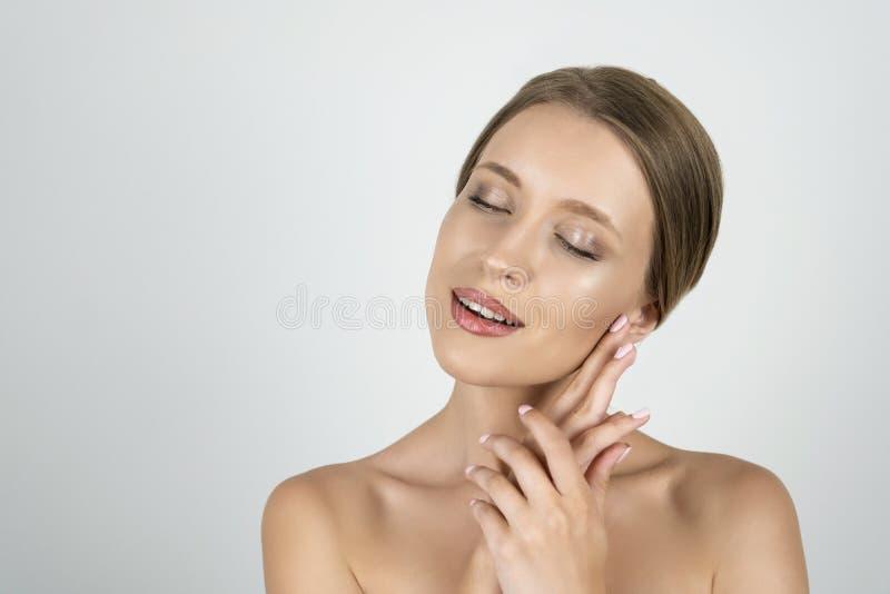 Belle jeune moitié blonde d'un tour de femme tenant des mains près de sa fin de menton vers le haut de fond blanc d'isolement photo stock