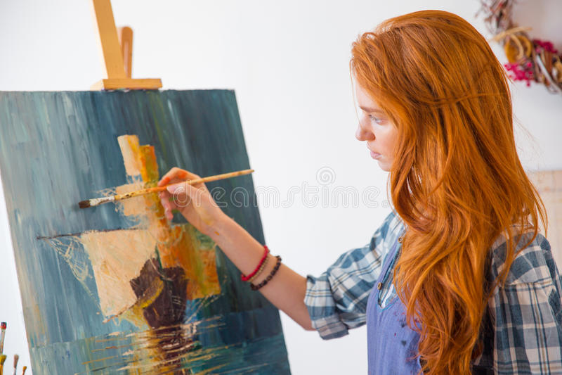 Belle jeune photo femelle sereine de peinture de peintre dans l'atelier d'art images libres de droits