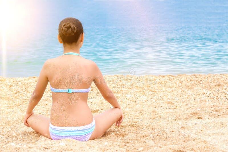 Belle jeune plage de mer d'?t? de m?ditation de yoga de pratique en mati?re de fille d'adolescent photos stock
