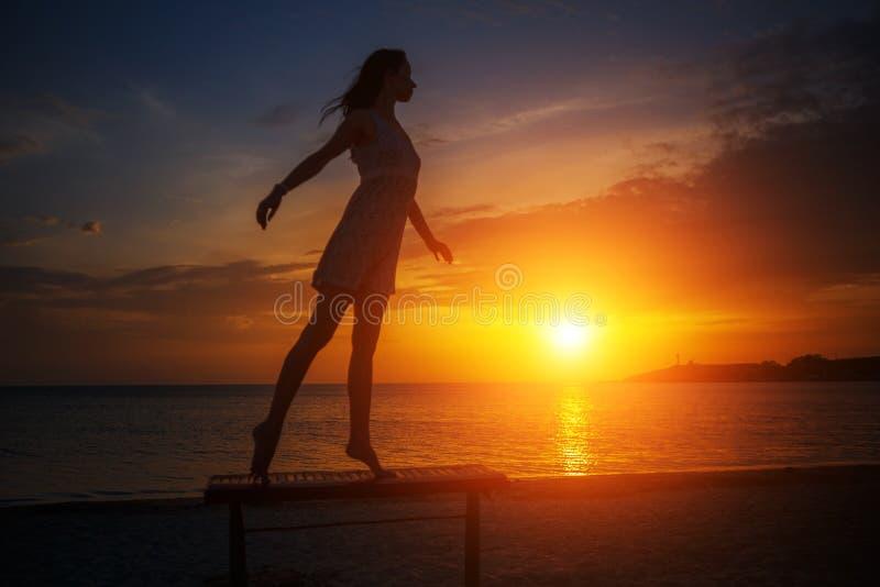 Belle jeune position mince de femme sur la plage au coucher du soleil, belle silhouette contre le ciel images stock