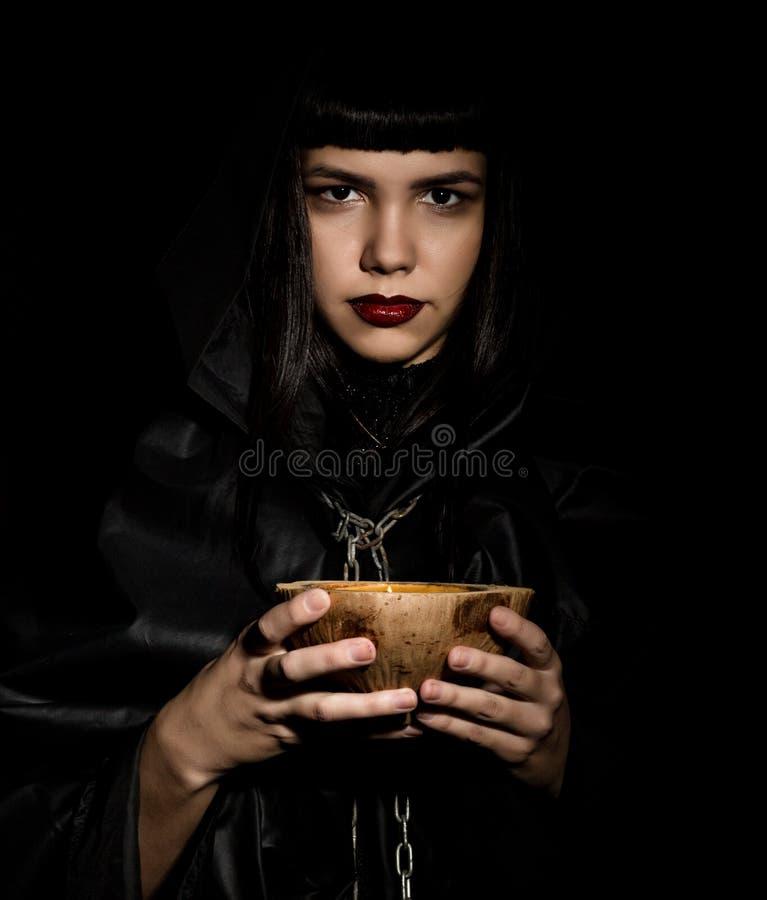Belle jeune sorcière avec une bougie de charmes photographie stock libre de droits