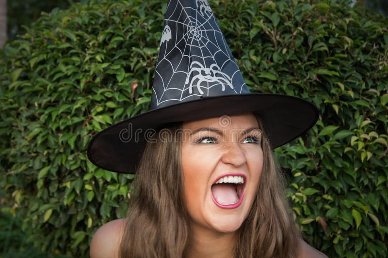 Belle jeune sorcière dans le chapeau noir criant photo libre de droits