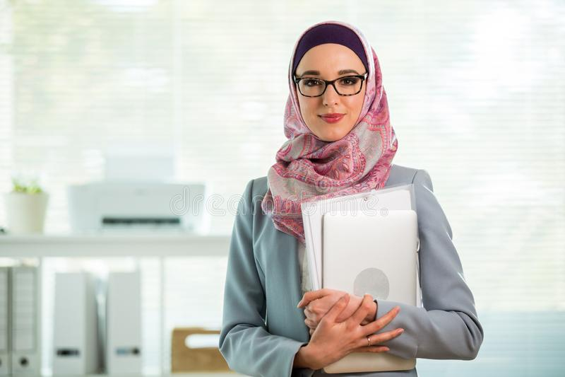 Belle jeune travailleuse active dans le hijab et lunettes souriant dans le bureau images libres de droits