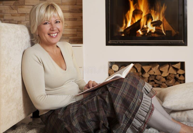 Belle lecture de femme par la cheminée à la maison photographie stock libre de droits
