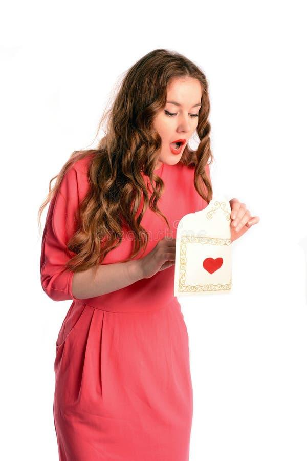 Belle lettre étonnée de valentine d'ouverture de jeune femme, d'isolement sur le fond blanc image stock