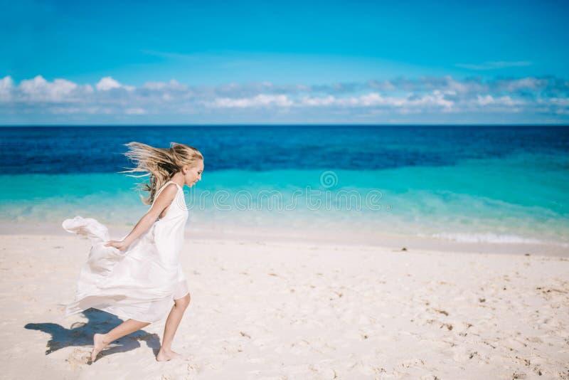 Belle longue jeune mariée blonde de cheveux dans la longue robe blanche fonctionnant sur la plage blanche de sable photographie stock