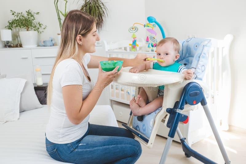 Belle mère alimentant son bébé garçon dans le highchair avec le gruau photos stock