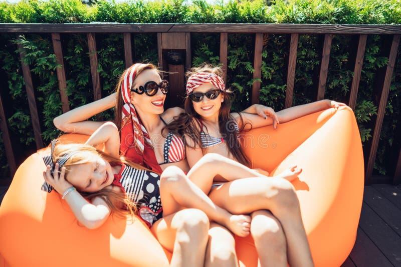 Belle mère avec deux filles s'asseyant sur un salon orange images libres de droits