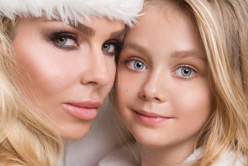 Belle mère blonde sexy avec une fille de bébé habillée comme Santa Claus photo stock