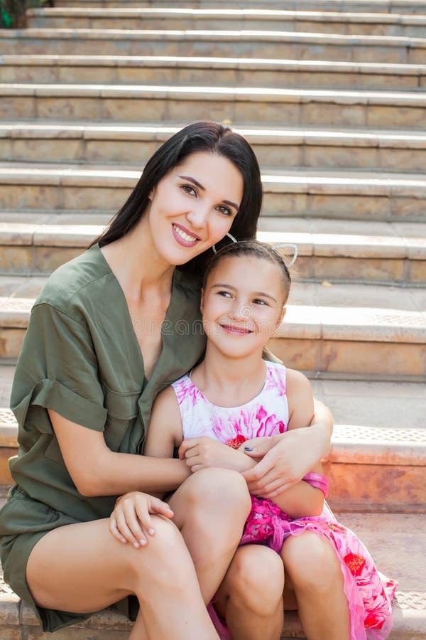 Belle mère et jeune fille s'asseyant sur des étapes images stock