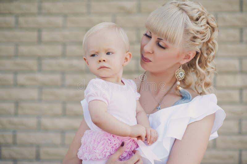 Belle mère heureuse étreignant le bébé avec le fond d'été d'amour dehors photographie stock